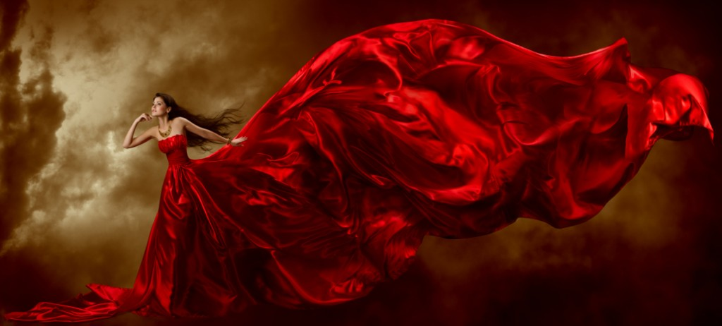 Woman in red waving beautiful dress with flying fabric over arti